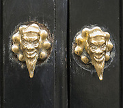 Ornate sculptured brass door handles in the appearance of the devil