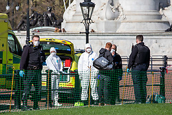 © Licensed to London News Pictures. 16/03/2020. London, UK. Police and medics in masks and protective suits outside Buckingham Palace talk to a man (2R). It is not clear if he is being arrested. Government ministers warn that the over 70s could face self-isolation for weeks as the Coronavirus disease pandemic continues . Photo credit: Alex Lentati/LNP