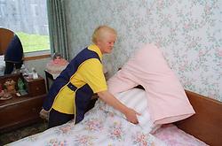 Elderly carer making bed for client,