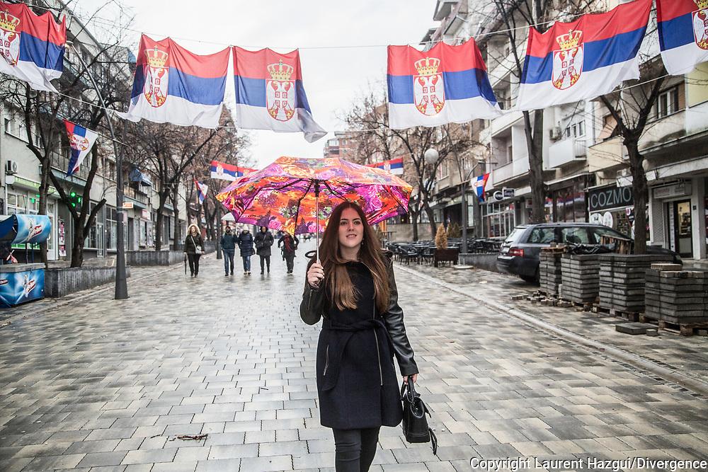 Décembre 2017. Kosovo : 10ème anniversaire de l'indépendance. Mirovica nord, partie serbe. Aleksandra Saška Lazarević, serbe, 20 ans, vit dans une enclave serbe proche de Mitrovica. Elle est très croyante et se rend régulièrement à l'église orthodoxe Saint-Dimitri située au nord de la ville appelé Kosovska Mitrovica par les Serbes. Elle étudie à l'International business collège, une école de commerce créée par l'ONG néerlandaise Spark pour rapprocher les communautés serbes et albanaises. Elle a plusieurs amis albanais, provoquant l'incompréhension de son entourage. Mais comme la majorité des serbes des enclaves, elle ne reconnaît pas l'indépendance du Kosovo. Des drapeaux serbes partout dans le nord de la ville.