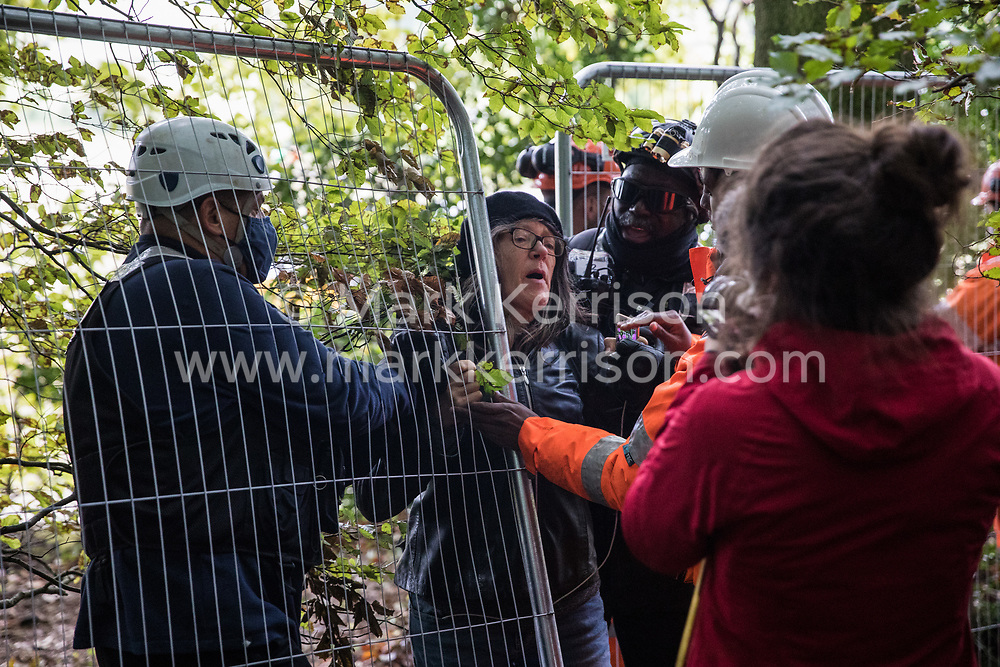 Aylesbury Vale, UK. 1st October, 2020. National Eviction Team bailiffs working on behalf of HS2 Ltd push an anti-HS2 activist through a fence during evictions from a wildlife protection camp in the ancient woodland which inspired Roald Dahl's Fantastic Mr Fox at Jones' Hill Wood. Around 40 environmental activists and local residents, some of whom living in makeshift tree houses 60 feet above the ground, were present during the evictions at Jones' Hill Wood which had served as one of several protest camps set up along the route of the £106bn HS2 high-speed rail link in order to resist the controversial infrastructure project.