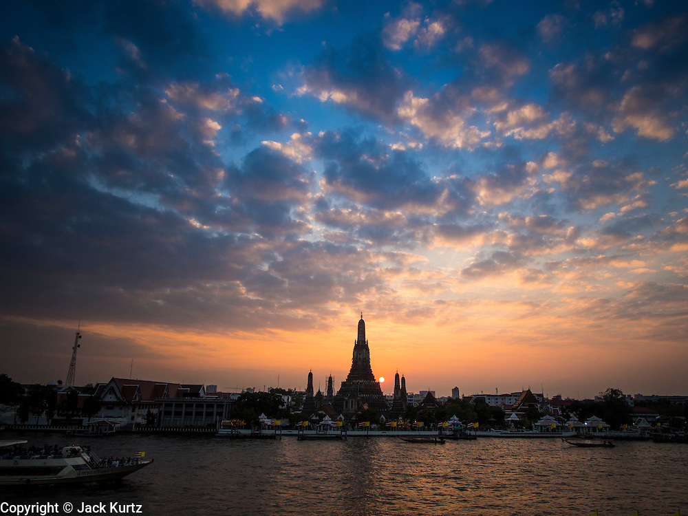 """19 DECEMBER 2013 - BANGKOK, THAILAND:  Wat Arun at the end of the day. Wat Arun Ratchawararam Ratchawaramahawihan or Wat Arun (""""Temple of Dawn""""), a Buddhist temple (wat) in Bangkok Yai district of Bangkok, on the Thonburi side of the Chao Phraya River. The temple derives its name from the Hindu god Aruna, often personified as the radiations of the rising sun. Wat Arun is among the best known of Thailand's landmarks and the first light of the morning reflects off the surface of the temple with pearly iridescence. Although the temple had existed since at least the seventeenth century, its distinctive Khmer style prang (spires) were built in the early nineteenth century during the reign of King Rama II.        PHOTO BY JACK KURTZ"""
