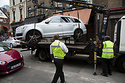 Car being lifted onto the back of a truck and impounded by Authorised Enforcement Unit for illegal parking in Spitalfields, London, UK. Rather than giving parking fines, this department removes the vehicle parked illegally.