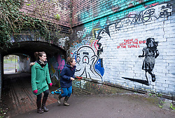 "© Licensed to London News Pictures; 14/03/2021; Bristol, UK. People walk past a mural in the style of Banksy with an image of a girl and with the words ""There is light at the end of the tunnel"", is seen next to a tunnel under the railway off Muller Road in Bristol. According to some locals it has been painted very recently, perhaps early this morning. Banksy often comments on current events, and if the piece is by Banksy it could be a reference to the end of the covid-19 coronavirus pandemic, or to social movements such as #MeToo, Black Lives Matter, or Reclaim the Streets. Photo credit: Simon Chapman/LNP."