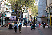 People wearing face masks in Birmingham city centre eerily quiet and deserted on New Street, one of the normally busy shopping areas, under lockdown due to Coronavirus on 24th April 2020 in Birmingham, England, United Kingdom. Coronavirus or Covid-19 is a new respiratory illness that has not previously been seen in humans. While much or Europe has been placed into lockdown, the UK government has extended stringent rules as part of their long term strategy, and in particular social distancing, which has left usually bustling areas like a ghost town.