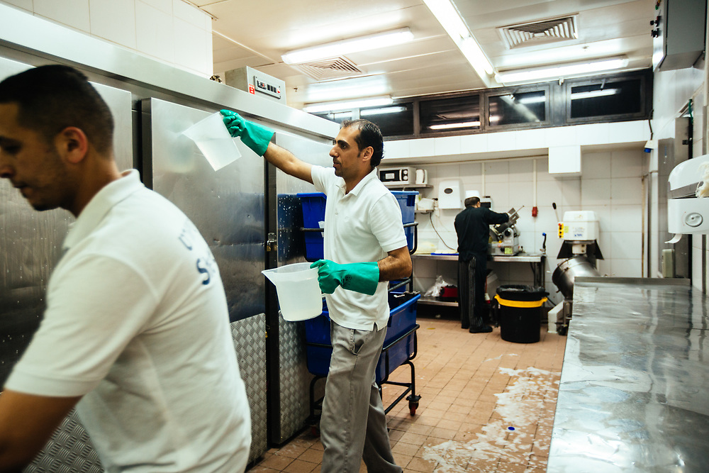 Ahmed Elshuk, 37 (C), a Jordanian employee from Amman and Muhammad Alsawi , 28 (L), a Jordanian employee from Aqaba are seen cleaning the kitchen of the Isrotel Lagoona Hotel in Eilat, southern Israel, on March 14, 2018.