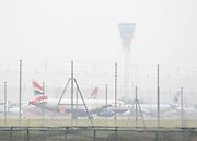 © Licensed to London News Pictures. 21/11/2011, Heathrow, UK.  Planes beneath a fog bound control tower. Flight delays continue at London's Heathrow Airport today. By 6.30am today a total of 21 flights from Heathrow were already cancelled affecting destinations including Manchester, Glasgow, Amsterdam, Brussels, Stockholm, Cologne and Nice.. Photo credit : Stephen Simpson/LNP