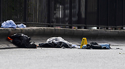 © Licensed to London News Pictures. 07/07/2016. London, UK. Evidence markers and personal belongings at the scene where a man was struck by a car following an assault on Harrow Road in Harlesden, north west London. Photo credit: Ben Cawthra/LNP