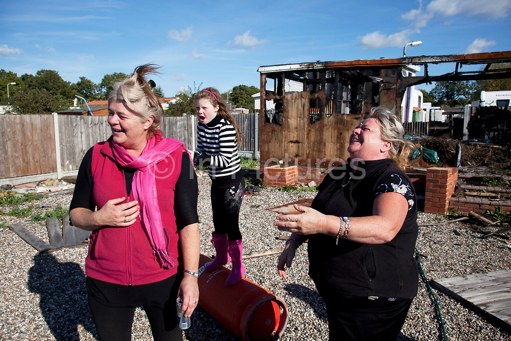 Mary McCarthy (r) laughing in defiance at the situation at Dale Farm site prior to eviction. Riot police and bailiffs were present on 20th October 2011, as the site was cleared of the last protesters chained to barricades. Dale Farm is part of a Romany Gypsy and Irish Traveller site in Crays Hill, Essex, UK. <br /> <br /> Senior resident Kathleen McCarthy said she now wished to leave, once obstacles are removed, and the majority of residents are expected to join her. Most plan to relocate to Oak Road, on the neighbouring legal site.<br /> <br /> Dale Farm housed over 1,000 people, the largest Traveller concentration in the UK. The whole of the site is owned by residents and is located within the Green Belt. It is in two parts: in one, residents constructed buildings with planning permission to do so; in the other, residents were refused planning permission due to the green belt policy, and built on the site anyway.