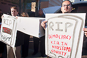"""05 DECEMBER 2009 -- PHOENIX, AZ: MANUEL DELGADO (right) and other protestors hold the coffin of """"civil rights"""" during a protest in front of the Maricopa County Board of Supervisors offices in Phoenix, AZ, Monday. About 200 people from several Phoenix area civil rights groups held a mock """"funeral"""" for civil rights in Phoenix Monday to protest actions taken by the Maricopa County Board of Supervisors recent decisions that limit protestors' ability to speak out against Sheriff Joe Arpiao during Board of Supervisors meetings. The protestors have been attending meetings to protest the Sheriff's series of anti-immigrant sweeps in Latino neighborhoods of Phoenix. Photo by Jack Kurtz / ZUMA Press"""