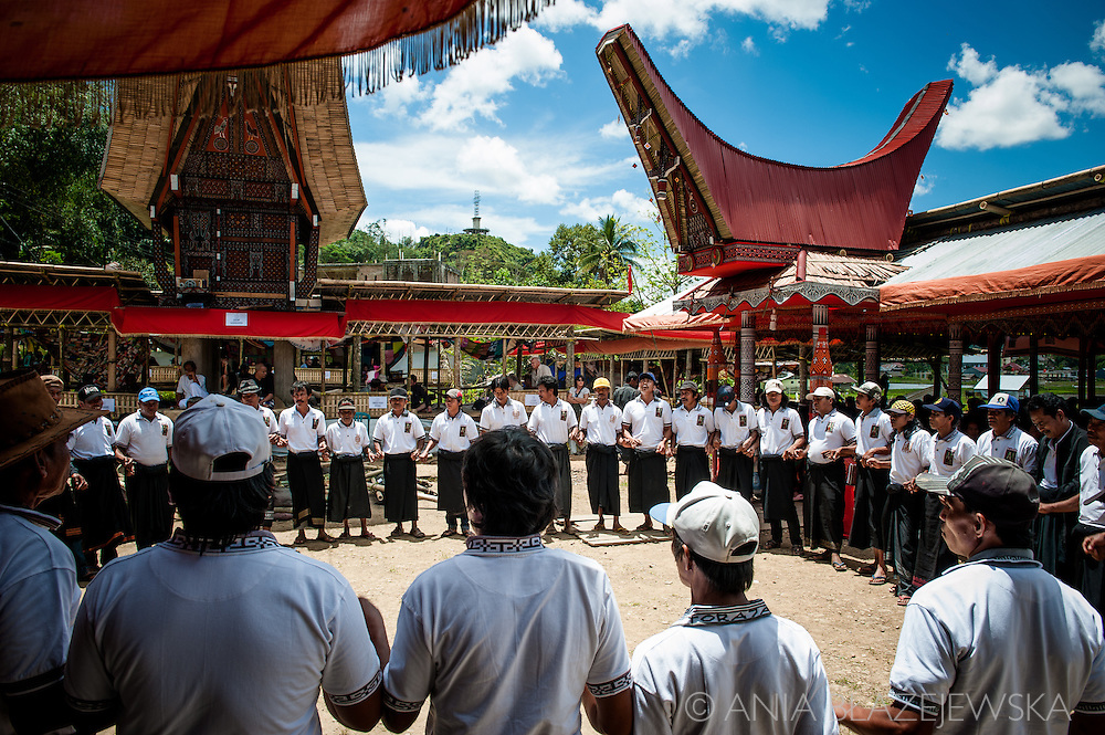 """Indonesia, Sulawesi. Receiving - the day when funeral guests arrive to attend a ceremony in Tana Toraja.<br /> <br /> The most important ceremony in Tana Toraja is a funeral, because of the beliefs, that without proper funeral rites the soul of the deceased will be not only enter the second life, but also will bring a misfortune to the whole members of the family.<br /> Although Torajan funeral tradition can vary depending on a particular village, a typical ceremony lasts for 4 days. The first day is a procession, during which the deceased is visiting the whole village. Second day it's """"receiving"""", when all the guests arrive and are welcomed by the family members. The third day is the most bloody, because of the buffalo slaughtery (the Torajans believe that the animals should follow people in the second life). On the fourth day the body is taken to the grave."""