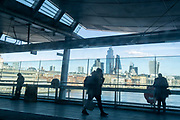Silhouetted rail travellers look out of the wide glass windows of Blackfriars Station that stretches across the river Thames, and which overlooks a panaorama of the City of London, the capital's financial district, on 26th February 2021, in London, England.