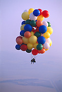 John Ninomiya, a cluster balloonist uses several hiking water bladders strapped on his side to control his rate of descent.