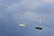 Two chairlift chairs meet above the clouds at ski field Turoa. Turoa is located on active volcano Mount Ruapehu, New Zealand.