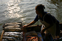 Grilling Fish at Taling Chan Floating Market, located on the canal Khlong Chak Phra and open only on weekends.  Orchard produce such as fruits, and vegetables, as well as fish are sold from boats. The idea for the floating market here was initiated in 1987 to honor King Bhumibol's 60th birthday. This is a new attraction since floating markets, an old way of life for Thai people, had vanished from Bangkok for some time only to be revived at Taling Chan