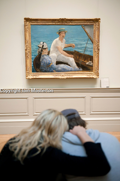 Couple looking at painting Boating by Edouard Manet at the Metropolitan Museum of Art in Manhattan , New York City, USA
