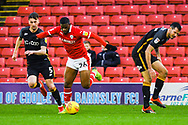 Mamadou Thiam of Barnsley (26) gets past two defenders during the EFL Sky Bet League 1 match between Barnsley and Bradford City at Oakwell, Barnsley, England on 12 January 2019.