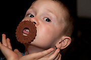 Polish boy age 6 substituting a round cookie for a mustache. Zawady Central Poland