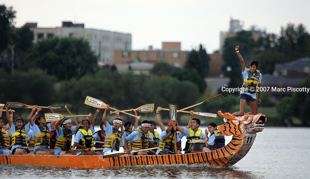 SHOT 7/29/2007 - Flag catcher Valerie Amphonephong (on bow of boat), 13, of Aurora raises her arm in victory as the rest of her Lao Buddhist Temple teammates celebrate their win in the championship of the youth division of the 2007 Colorado Dragon Boat Festival. The sport of Dragon boat racing is over 2000 years old and features teams of 18 paddlers - nine men and nine women plus someone to steer the boat - all rowing in sync to the beat of a drum and racing to a flag 200 meters away on Sloan's Lake in Denver, Co. Founded in 2001 to celebrate Denver?s rich Asian Pacific American culture, the Colorado Dragon Boat Festival has become the region?s fastest growing and most acclaimed new festival. Festival-goers get to explore the Asian culture through demonstrations, crafts, shopping, eating, and the growing sport of dragon boat racing. .(Photo by Marc Piscotty / © 2007)