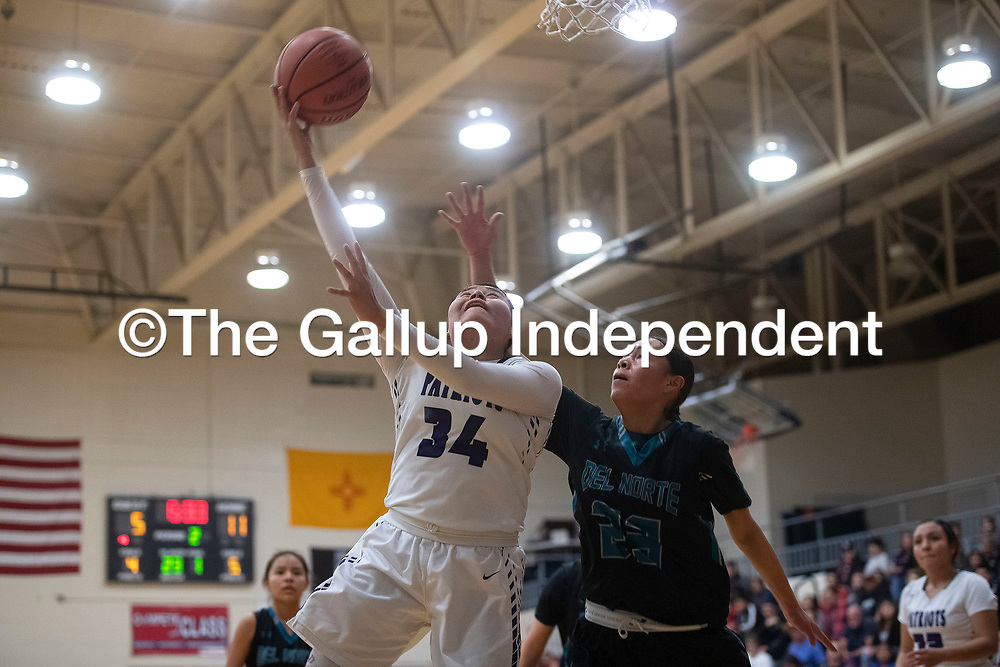 Miyamura's Tatum Bennett (34) drives to the basket for a layup as Del Norte's Kayden Washington (23) defends Friday night at Miyamura High School in Gallup.