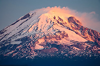 Clouds form and stream from above Mount Adams in morning alpenglow as viewed from the south side near Glenwood, Klickitat County, WA, USA.