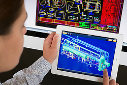 Engineer using iPad application to model 3D design of complex industrial design of patrochemical plant