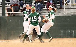 30 March 2013:  Katie Crane pulls in a popped up ball in front of Chloe Montgomery and Emma Clark during an NCAA Division III women's softball game between the DePauw Tigers and the Illinois Wesleyan Titans in Bloomington IL<br /> <br /> Umpire is Jay MacDaniels of Pekin IL