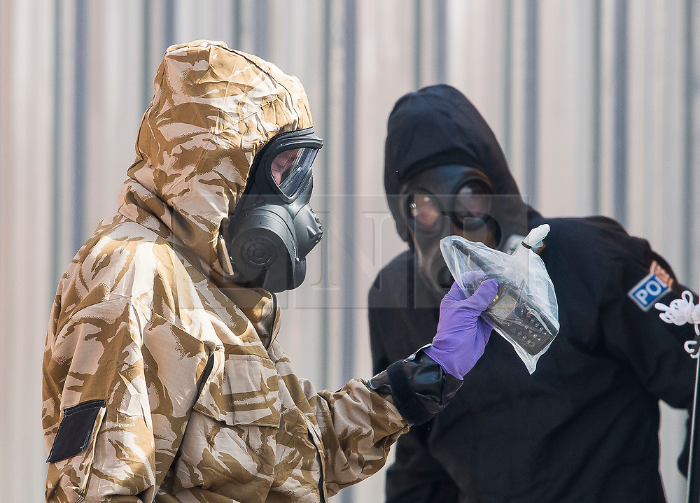 © Licensed to London News Pictures. 06/07/2018. Salisbury, UK. A member of a military specialist team wearing a hazmat suit is seen carrying a walkie talkie or mobile phone in a bag while leaving John Baker House in Salisbury, Wiltshire an area visited by two people who are in critical condition after being exposed to the Novichok nerve agent. Dawn Sturgess, 44, and Charlie Rowley, 45 have been confirmed as having come in to contact with the deadly agent after samples were sent to the MoD's Porton Down laboratory. Former Russian spy Sergei Skripal and his daughter Yulia were poisoned with Novichok nerve agent in nearby Salisbury in March 2018 causing diplomatic tentions between Russia and the UK. Photo credit: Ben Cawthra/LNP