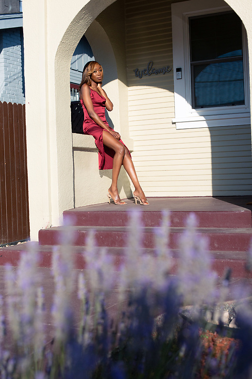 Tolulobe Afolabi, 29, poses in front of her cousin's house in Oakland, California, where she is originall from. An advocate for sickle cell anemia awareness, she chose to wear a dress of burgandy, the ribbon color for the cause. June 29, 2021.//Photograh by Nathan Weyland