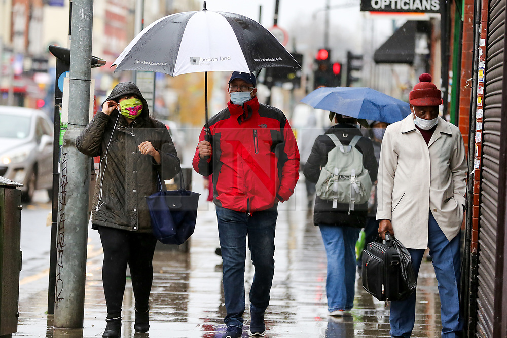 © Licensed to London News Pictures. 14/11/2020. London, UK. Members of the public shelter from rain underneath umbrellas in north London. The Met Office has issued a yellow weather warning for the UK for heavy rain and strong winds, as up to 20 days worth of rain is expected to fall in the next few days. Photo credit: Dinendra Haria/LNP