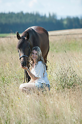 Young woman stroking her brown horse sitting on meadow and smiling, Bavaria, Germany