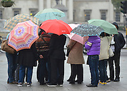 © Licensed to London News Pictures. 25/10/2012. Westminster, UK Tourists with umbrellas stand in the rain at Trafalgar Square today 25 October 2012. Photo credit : Stephen Simpson/LNP