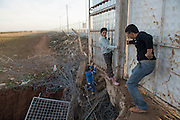 Syrian - Turkish border in Kilis, smuglers and FSA fighter from Liwa Al Tawaeed brigade open fence in the Turkish border to cross the border illegally.  Because Turkey is saturated with refugees, they will likely get no  help, no work, and no place in a refugee camp. Many refugees return to Aleppo after a few month in Turkey, a country that is now saturated with refugees