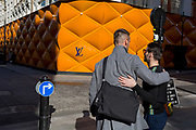 Friends greet each other opposite the temporary renovation hoarding of luxury brand Louis Vuitton in New Bond Street, on 25th February 2019, in London, England.