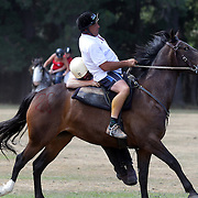 A competitor struggles to mount his horse during the 50th Anniversary Glenorchy Race meeting. The races, which originally started in the 1920's, were resurrected in 1962 and have been run by local farmers and the rugby club on the first Saturday after New Years Day ever since. Glenorchy, Otago, New Zealand. 7th January 2012