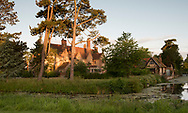 A 12th century moat surrounding the garden and Tudor manor house at sunrise at Hindringham Hall, Hindringham, Norfolk