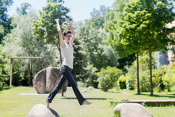 Mature woman jumping from one rock to another rock in the park, Freiburg im Breisgau, Baden-Wuerttemberg, Germany