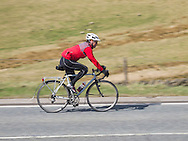 Cyclist descending the hill from the Cat n Fiddle, Peak District National Park