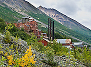 """The 14-story Kennecott Concentration Mill processed copper ore 1911-1938. Kennecott Mines National Historic Landmark and nearby McCarthy nestle under Bonanza Ridge in the Wrangell Mountains within Wrangell-St. Elias National Park and Preserve, in Alaska, USA. Old mine buildings, artifacts, and colorful history attract summer visitors. Remote McCarthy is connected to Chitina via the McCarthy Road spur of the Edgerton Highway. After copper was discovered between the Kennicott Glacier and McCarthy Creek in 1900, the Kennecott town, mines, and Kennecott Mining Company were created and named after the adjacent glacier. Kennicott Glacier and River had previously been named after Robert Kennicott, a naturalist who explored in Alaska in the mid-1800s. The corporation and town stuck with a mistaken spelling of """"Kennecott"""" with an e (instead of """"Kennicott"""" with an i). Partly because alcoholic beverages and prostitution were forbidden in the company town of Kennecott, the neighboring town of McCarthy grew quickly to provide a bar, brothel, gymnasium, hospital, and school. The Copper River and Northwestern Railway reached McCarthy in 1911 to haul over 200 million dollars worth of ore 196 miles to the port of Cordova on Prince William Sound. By 1938, the world's richest concentration of copper ore was mostly gone, the town was mostly abandoned, and railroad service ended. Not until the 1970s did the area began to draw young people for adventure and the big money of the Trans Alaska Pipeline project. Declaration of Wrangell-St. Elias National Park in 1980 drew adventurous tourists who helped revive McCarthy with demand for needed services. Wrangell-St. Elias National Park and Preserve (the largest National Park in the USA) is honored by UNESCO as part of a World Heritage Site. This image was published in 2019 in a permanent exhibit for the Alaska Public Lands Information Center in Anchorage."""