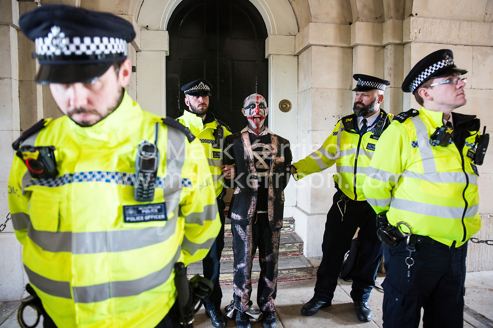 London, UK. 7 October, 2019. Metropolitan Police officers arrest a Brazilian climate activist from Extinction Rebellion in Horseguards on the first day of International Rebellion protests to demand a government declaration of a climate and ecological emergency, a commitment to halting biodiversity loss and net zero carbon emissions by 2025 and for the government to create and be led by the decisions of a Citizens' Assembly on climate and ecological justice.