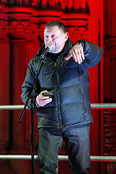 "© Licensed to London News Pictures . 03/02/2015 . Manchester , UK . Madchester star SHAUN RYDER reads a short speech from his phone to the crowd , at the demonstration . Demonstration organised by the Labour Party on the steps of Manchester City Council in Albert Sqaure , Manchester , under the banner ""manVcam"" ( Manchester vs Cameron ) . Organisers say Manchester - along with Liverpool and Birmingham - have suffered larger cuts than other regional authorities , whilst southern regions such as Surrey , Hampshire and West Sussex have all seen increases in government funding . Photo credit : Joel Goodman/LNP"