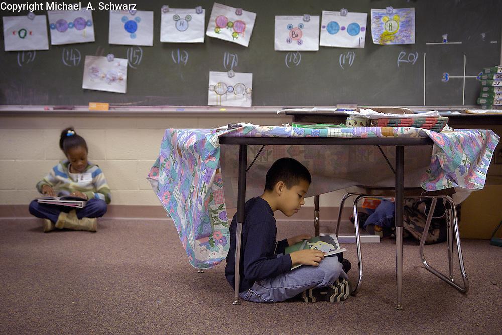 Marietta, GA January 14, 2006<br /> <br /> Omosaze  reading program<br /> <br /> Miquel Macias finds a quiet spot under a desk to read.  Some photos have Kelsea Duncan in background.