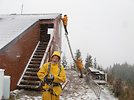 Leyton shows his safety equipment for wrok on the roof as work proceeds through the first snowfall of the season on the Mount Tahoma Trails Association's High Hut cross country ski trails cabin in the Tahoma State Forest, Ashford, WA