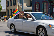 A woman waves a pride flag from a car window during the Mifflinburg Pride Event.