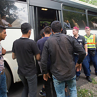 Illegal migrants from Afghanistan get on a bus under police custody near border town Asotthalom (about 190 km South-East of capital city Budapest), Hungary on July 16, 2015. ATTILA VOLGYI