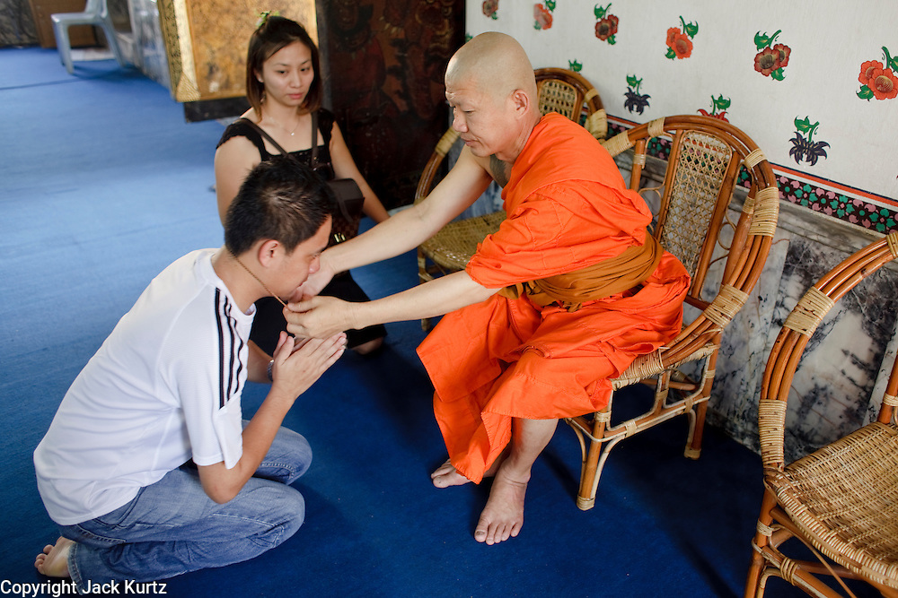 """Mar. 9, 2009 -- BANGKOK, THAILAND:  A monk blesses an amulet for a man and his girlfriend in Wat Arun in Bangkok. Wat Arun is a Buddhist temple (wat) in the Bangkok Yai district of Bangkok, Thailand, on the west bank of the Chao Phraya River. The full name of the temple is Wat Arunratchawararam Ratchaworamahavihara. The outstanding feature of Wat Arun is its central prang (Khmer-style tower). It may be named """"Temple of the Dawn"""" because the first light of morning reflects off the surface of the temple with a pearly iridescence. Steep steps lead to the two terraces. The height is reported by different sources as between 66,80 m and 86 m. The corners are surrounded by 4 smaller satellite prangs. The prangs are decorated by seashells and bits of porcelain which had previously been used as ballast by boats coming to Bangkok from China. The central prang is topped with a seven-pronged trident, referred to by many sources as the """"trident of Shiva"""". Around the base of the prangs are various figures of ancient Chinese soldiers and animals. Over the second terrace are four statues of the Hindu god Indra riding on Erawan. The temple was built in the days of Thailand's ancient capital of Ayutthaya and originally known as Wat Makok (The Olive Temple). In the ensuing era when Thonburi was capital, King Taksin changed the name to Wat Chaeng. The later King Rama II. changed the name to Wat Arunratchatharam. He restored the temple and enlarged the central prang. The work was finished by King Rama III. King Rama IV gave the temple the present name Wat Arunratchawararam. As a sign of changing times, Wat Arun officially ordained its first westerner, an American, in 2005. The central prang symbolizes Mount Meru of the Indian cosmology. The satellite prangs are devoted to the wind god Phra Phai..Photo by Jack Kurtz / ZUMA Press"""