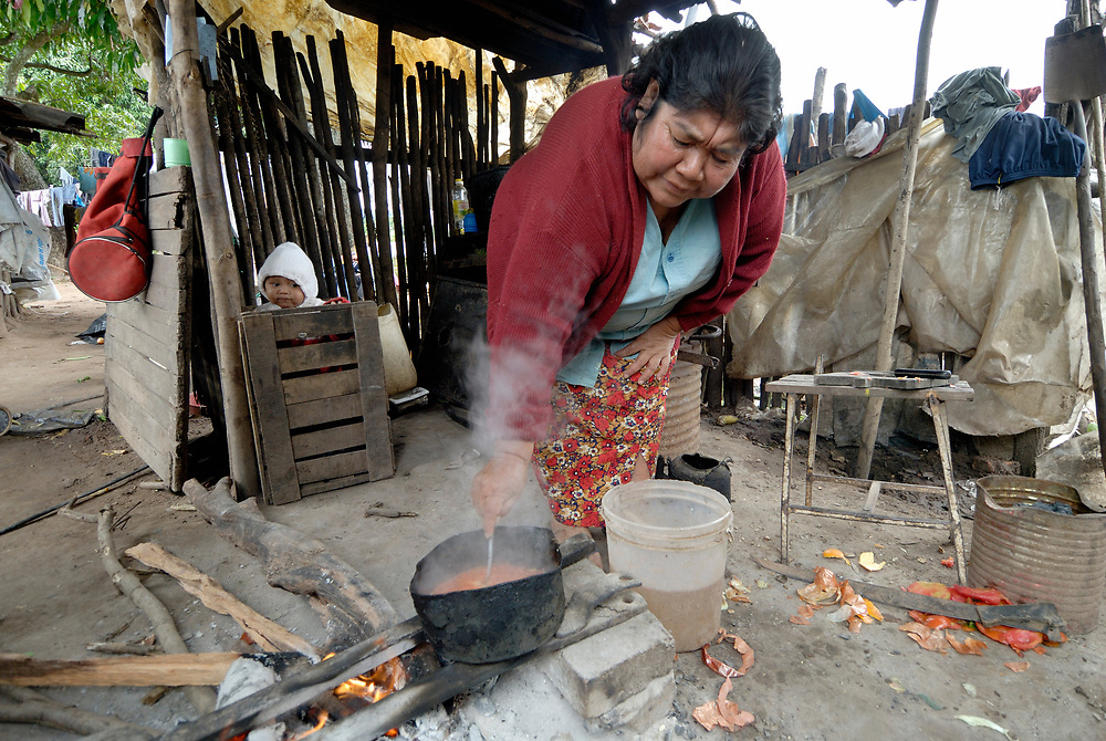 Juana Arroyo, a Guarani woman in El Bananal, Argentina, cooks a meal while a grandchild looks on.