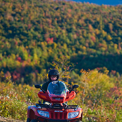 A man rides his ATV on a ridge at Jericho Mountain State Park in Berlin, New Hampshire.  The Presidential Range is in the distance. White Mountains.