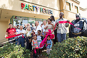 Mayor Jose Esteves and members of the Milpitas Chamber of Commerce cut the ribbon during the Milpitas Chamber of Commerce Ribbon Cutting Ceremony at Party Fever in Milpitas, California, on July 31, 2014. (Stan Olszewski/SOSKIphoto)
