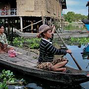 Women in canoe paddling through fishing village (Siem Reap, Cambodia - Oct. 2008) (Image ID: 081023-1702381a)